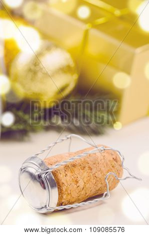 sparkling wine cork against decorative christmas gift boxes and balls on white surface