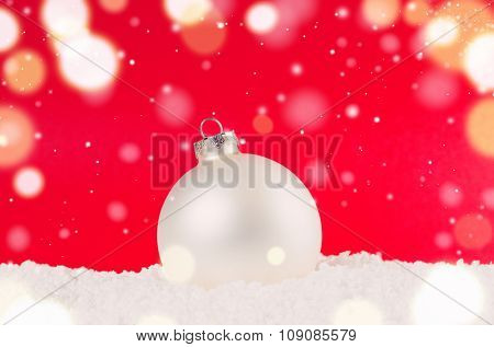 white decorative christmas ball on snow against red festive background