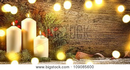 Burning candles with decorations on wood background