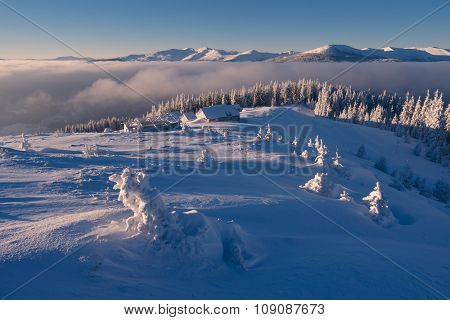 Winter landscape. Sunny morning with blue sky. Wooden houses in the mountains. Carpathians, Ukraine, Europe