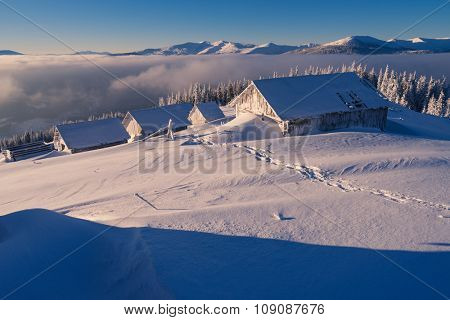 Winter landscape. Wooden houses in the snow. Mountain village of shepherds. Sunny weather in the morning. Carpathians, Ukraine, Europe