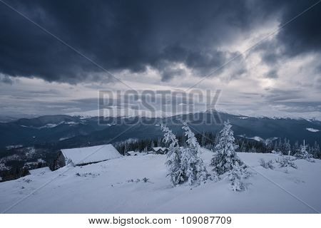 Bad weather in the mountains. Winter landscape. Cloudy evening with storm clouds. Wooden houses of shepherds under the snow. Carpathians, Ukraine, Europe
