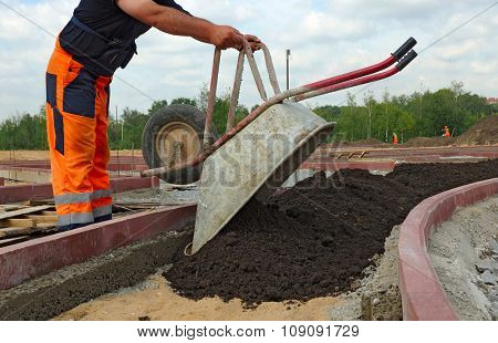 Worker pours the soil from the wheelbarrow.