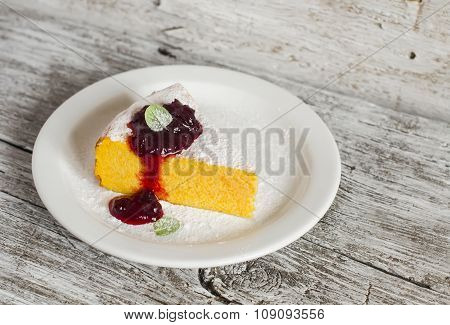Cottage Cheese And Pumpkin Casserole With  Berry Sauce On A White Plate On A Light Wooden Board