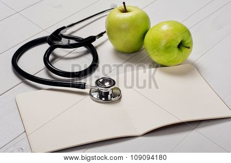 Open Notebook With A Stethoscope And Apple