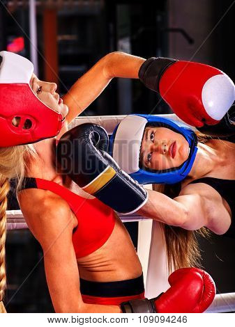 Two  women boxer wearing red  gloves to box in ring. Striking below the chin.