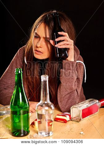 Drunk girl holding bottle of alcohol. Mess on table. Soccial issue alcoholism.