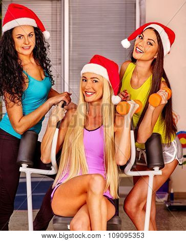 Young woman wearing santa hat  holding dumbbells in sport gym. Sport Christmas concept