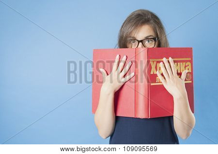 Girl With Glasses Peeping From Behind A Big Book..