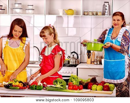 Family with grandmother and female kid cooking at kitchen.