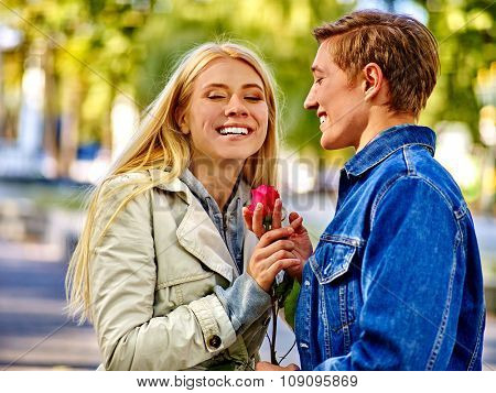 Young couple hugging and flirting in  park  and looking up. Woman holding red rose.