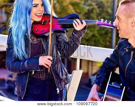 Music street performers  with happy smiling girl violinist and man guitarist on blue sky outdoor.