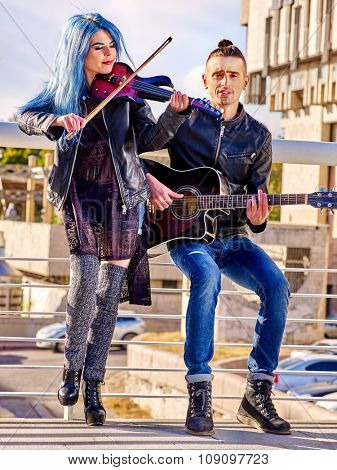 Music street performers wearing jeans with girl violinist and man guitarist on blue sky outdoor.