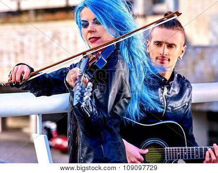 Music street performers  with  extravagant hairstyle girl violinist and man guitarist on blue sky outdoor.