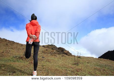 young woman trail runner running on mountain peak