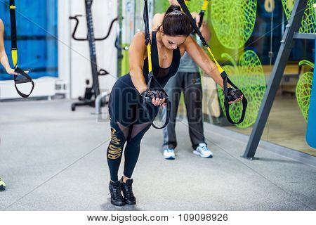 Young woman training exercise push ups with trx fitness straps in the gym  Concept sport workout hea