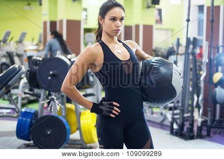 Muscular fit woman workout in gym. Strong female doing exercise with medicine ball fitness club.