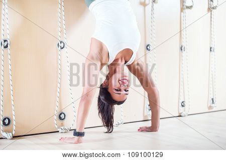 Fit woman doing handstand near wall. Athlete standing on hands Concept balance sport fitness.