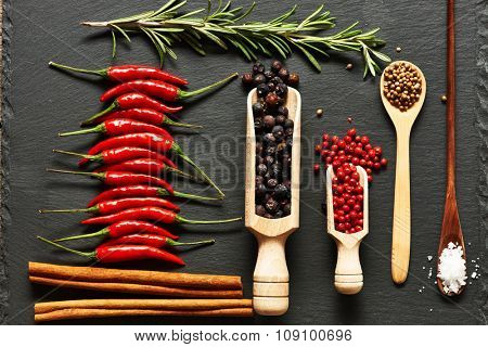 Red hot chili peppers and spices on slate background