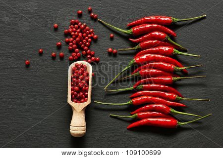 Red hot chili peppers and rose pepper on slate background