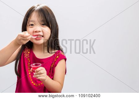 Kid Eating Gelatin Dessert / Kid Eating Gelatin Dessert Background / Studio Isolated Of Happy Kid Ea
