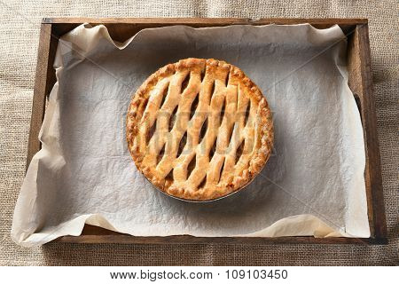 High angle view of an apple pie in a wood box lined with parchment paper. Horizontal format on a burlap table cloth.