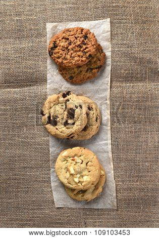 High angle view of three small stacks of fresh baked holiday cookies on a strip of parchment paper on burlap covered table. High angle view in vertical format.