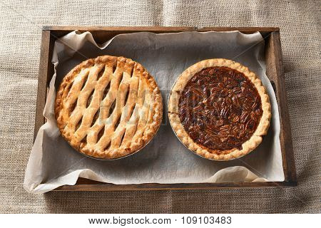 High angle view of an apple pie and pecan pie in a wood box lined with parchment paper. Horizontal format on a burlap table cloth.