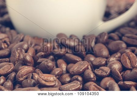Heap Of Coffee Beans And Part Of Coffee Cup At Background Vintage Filtered