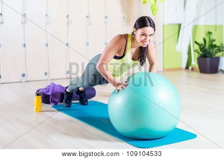 Fit woman doing push ups with medicine ball workout out arms Exercise training triceps and pectorals