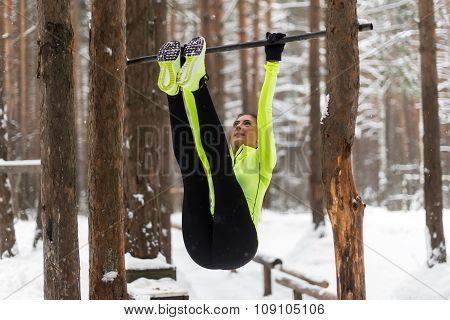 Fit girl training abs by raising legs on a horisontal bar. Fitness woman workout doing exercises out