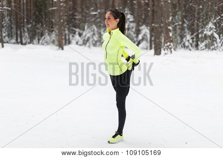 fit young woman stretching her leg before a run in forest or park.