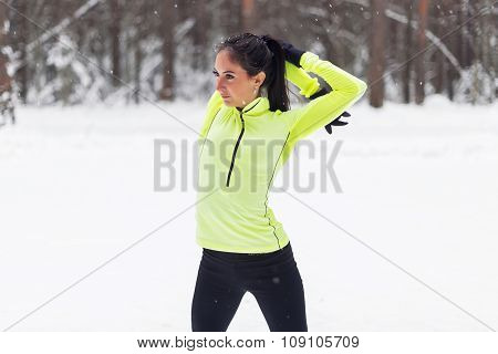 Athletic fit woman warming up in the forest Winter workout.
