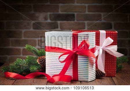 Christmas gift boxes and fir tree branch on wooden table