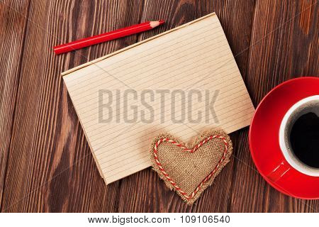 Valentines day toy heart, coffee cup and notepad for your text. Top view on wooden table