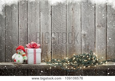Christmas lights, gift box and snowman toy in front of wooden wall with copy space