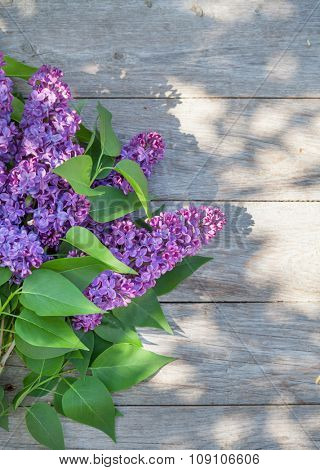 Purple lilac flowers on garden table. Top view with copy space