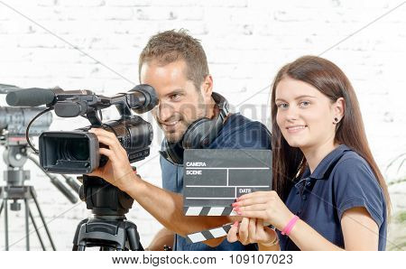 A Cameraman And A Young Woman With A Movie Camera And Clapper