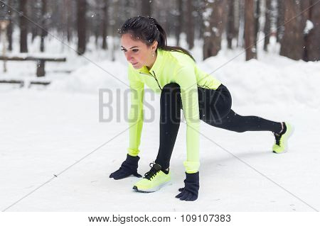 Fit woman runner stretching legs before workout warming up outdoor Winter park.
