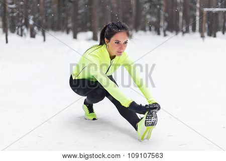 Fitness young woman stretching her legs outdoors Winter park forest.