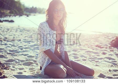 Beach woman wearing sunglasses Summer travel holidays vacation. girl in shirt and bikini sitting the