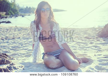 Young woman enjoying sunny day on tropical beach sitting in the sand toned instagram filter.