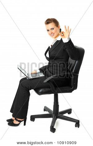 Smiling modern business woman sitting on chair with laptop and showing ok gesture