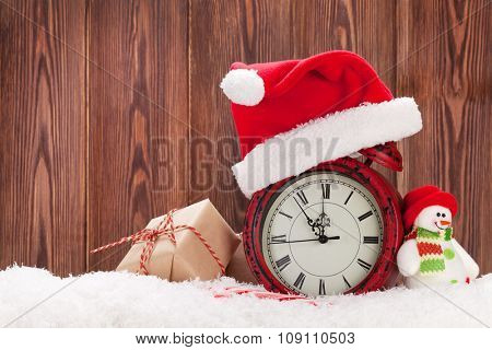 Christmas gift box, snowman toy and alarm clock in snow. View with copy space