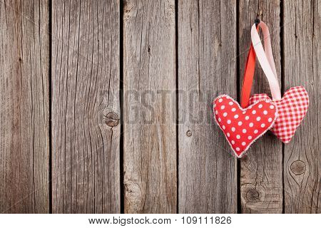 Two Valentines day hearts on rustic wooden wall with copy space