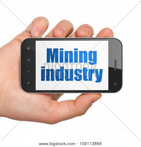 Industry concept: Hand Holding Smartphone with Mining Industry on display
