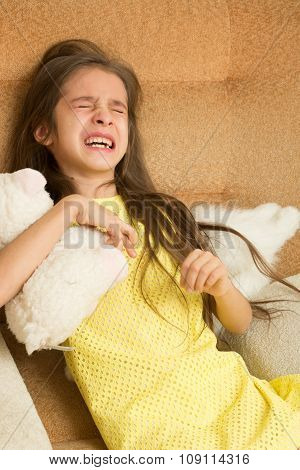 little girl crying on a chair.