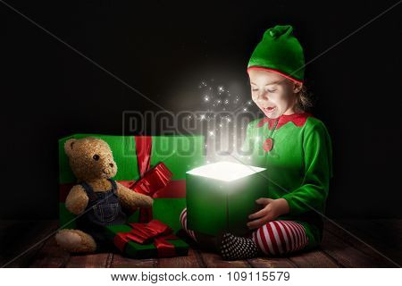 Cute little girl opening a magic gift box.