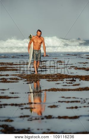 A man wearing surf shorts standing at the edge of a shallow reef looking out into the ocean as the sun sets. Tide pools and green seaweed in the foreground with flowing water.