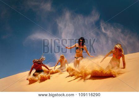 Crowd of friends slide down sandy dune  against blue sky